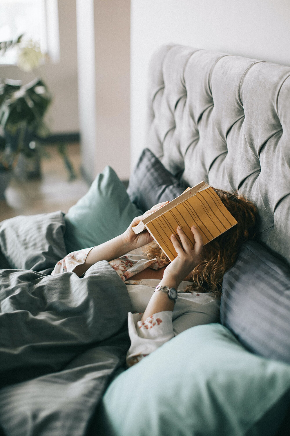 woman-covering-face-with-book-on-bed-1524232.jpg